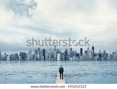 man looking at the town on a horizon