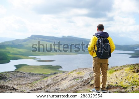 Man looking at view of impressive l cliffs on the Isle of Skye, Scotland