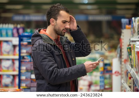 Man Looking Confused At Mobile Phone In Supermarket - stock photo