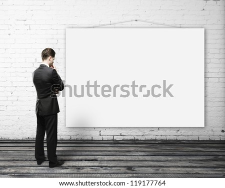 man looking empty poster on wall - stock photo