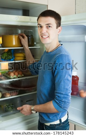 Man looking for something in pan near fridge at home