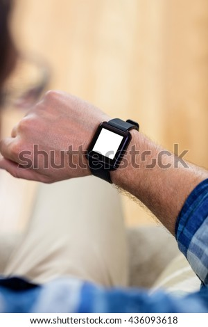 Man looking his smart watch at home - stock photo