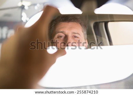 Man looking in an interior car mirror while sitting in a car