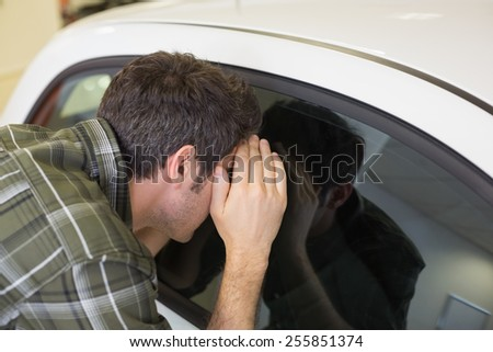 Man looking inside a car at new car showroom