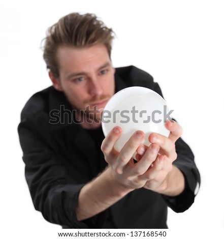 Man looking into a glass ball, wearing a black coat. White background. - stock photo