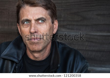 Man looking lonely next to a wooden fence. - stock photo