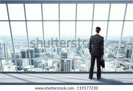man looking on city through the window - stock photo