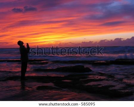 Man looking on sunset skys - stock photo