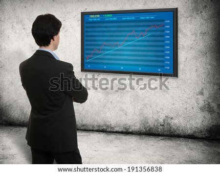 man looking on the screen with stock market graph