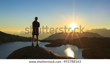 Man looking over a lake, Lac Cornu, during sunset.