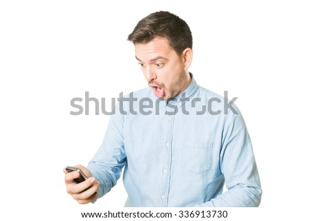 Man looking surprised to his phone - stock photo