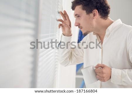 Man looking through blinds - stock photo
