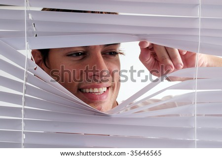 Man looking through blinds