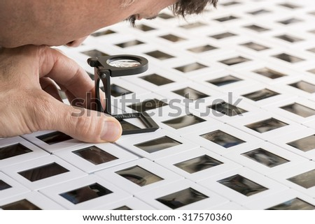 man looking through the loupe a series of slide - stock photo