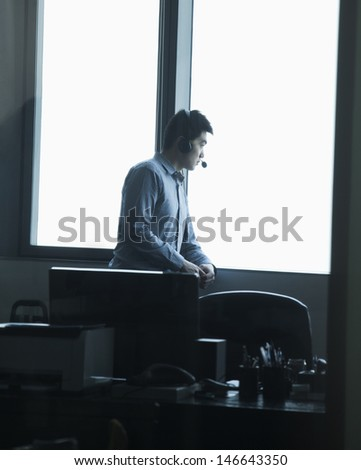 Man looking through window in office