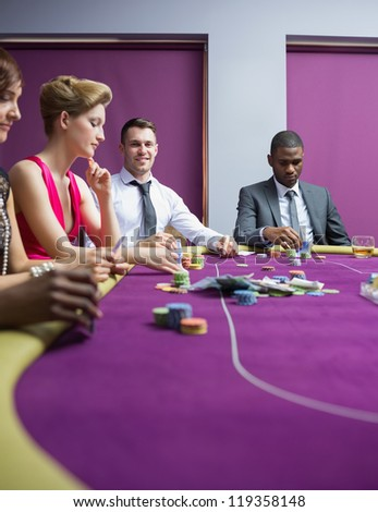 Man looking up and smiling at poker game - stock photo