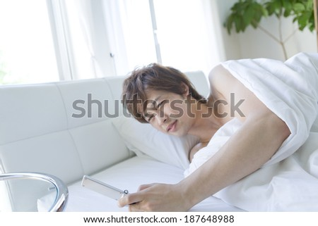 man looks at mobile phone when he just woke up - stock photo
