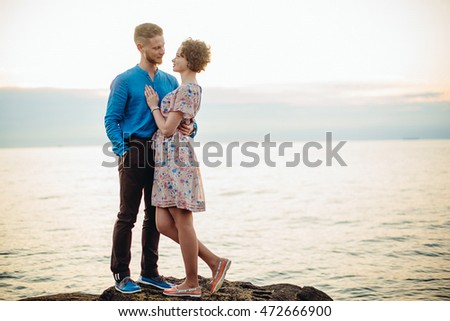 Man looks at woman with love posing by the sea
