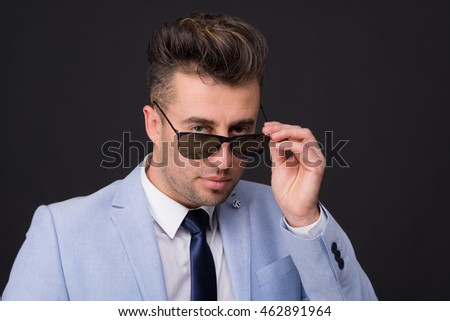 man looks casually over his glasses