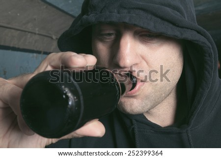 Man looks depressed with bottle in his hand. - stock photo