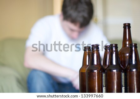 Man looks depressed with empty beer bottles - stock photo