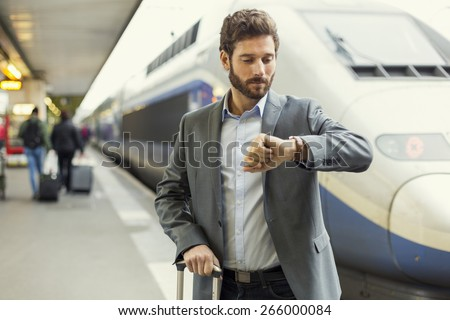 Man looks his watch on the platform station - stock photo