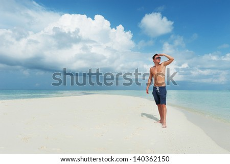 Man looks into the distance on the background of beautiful beach with white sand and cloudy sky - stock photo