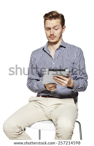 Man looks on tablet with incredulity. Studio shot.  - stock photo