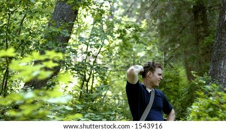 Man lost in forest with blue shirt - stock photo