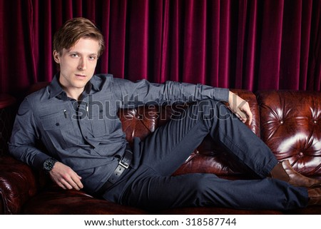Man lounging on a couch in a club - stock photo
