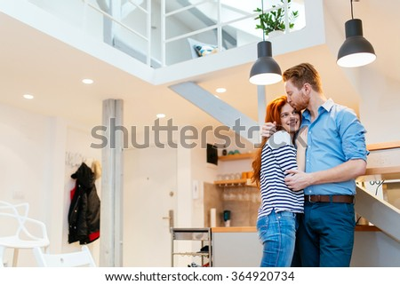 Man loving wife at home and hugging her with affection - stock photo