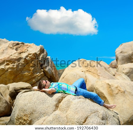 Man lying among the rocks on the beach and looking at a lonely cloud. Series Emotions / Feelings  #01 photos