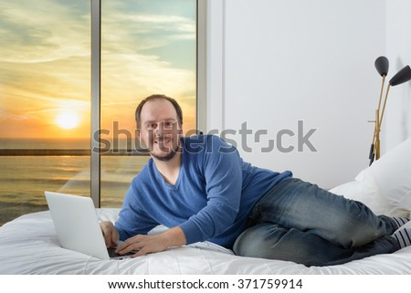 man lying bed smiling working on laptop computer sunset over ocean beach through window