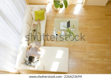 Man lying down on sofa in the living room - stock photo