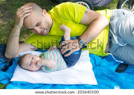 Man lying down with his son - stock photo