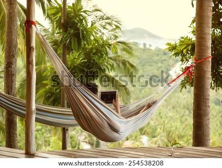 man lying in a hammock freelancer and running, beautiful mountain views, drinking wine - stock photo