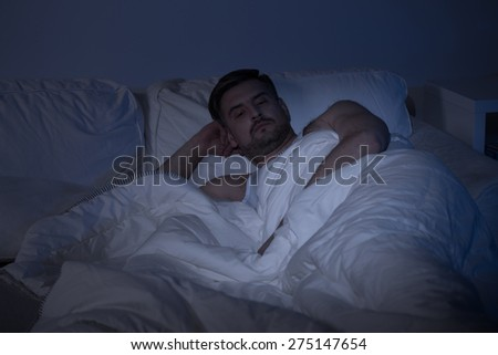 Man lying in bed with open eyes