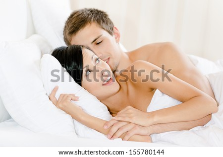 Man lying in bed with white linen embraces woman. Concept of love and affection