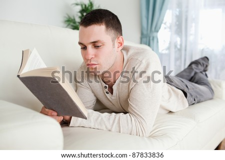 Man lying on a couch to read a book in his living room