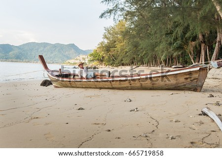 man lying on a thai longtail boat, on the beach in Thailand