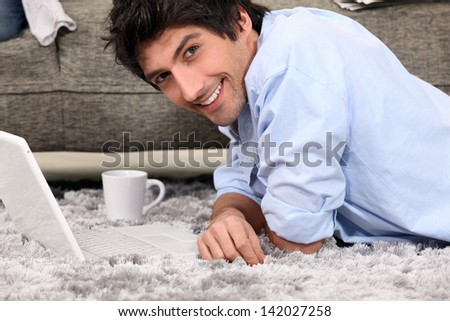 Man lying on carpet with coffee and computer - stock photo