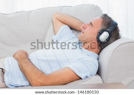 Man lying on couch listening to music at home in living room