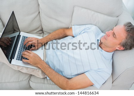 Man lying on couch typing on laptop at home in living room