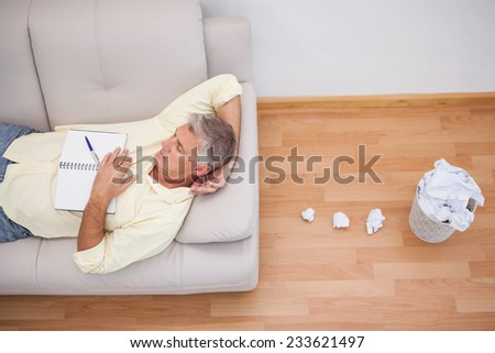 Man lying on couch with crumpled papers at home in the living room