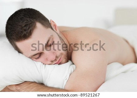 Man lying on his belly while sleeping in his bedroom - stock photo