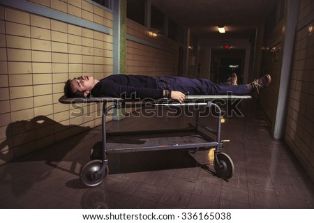 Man lying on medical patient stretcher in old horror hospital - stock photo