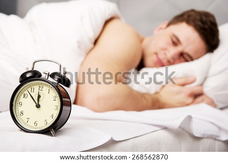 Man lying on the bed with alarm clock. - stock photo