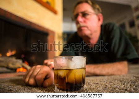 Man lying on the floor in front of a fireplace, with a drink in front of him.