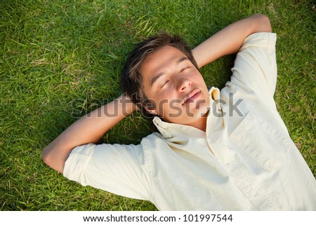 Man lying on the grass with his eyes closed and both hands resting behind his neck - stock photo