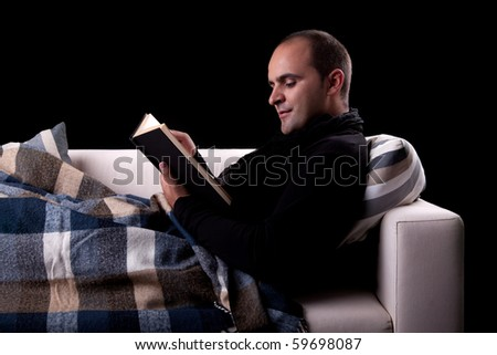 man lying on the sofa reading a book, isolated on black, studio shot. - stock photo